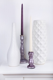 Candles in candle holders and vases on table on white