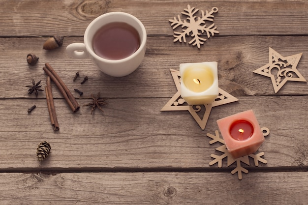 Candles and christmas decoration on wooden background