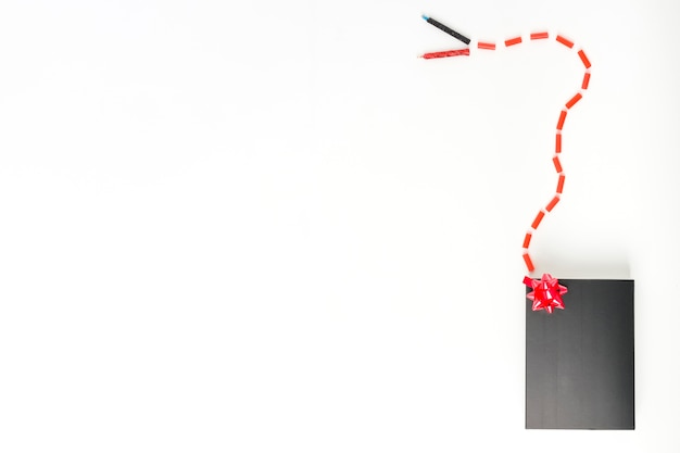 Candles connected with candies to black gift box with red decorative bow on white background