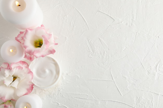 Candles, cream and flowers on white background, space for text