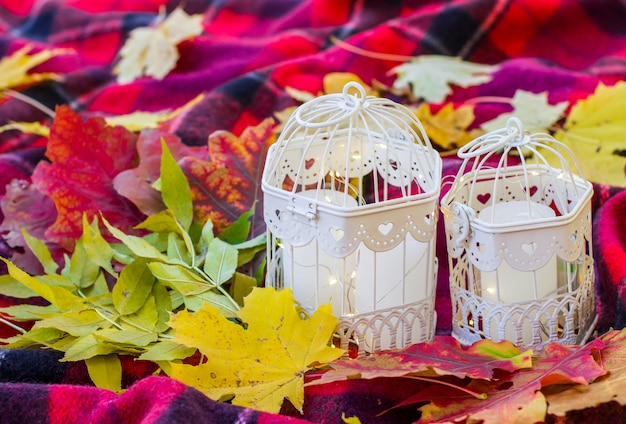 Candles in decorative cages on a blanket in the park