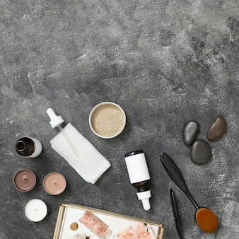 Candles; essential oil bottle; rhassoul clay; la stone; himalayan rock salt on tray against black concrete backdrop