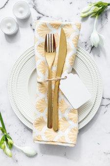 Candles; flower and white plate with folded napkin and cutlery on textured backdrop