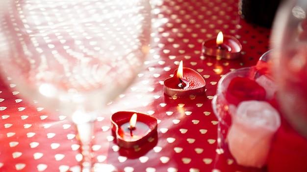 バレンタインデーのキャンドル、お祝いの赤い背景のテーブル。