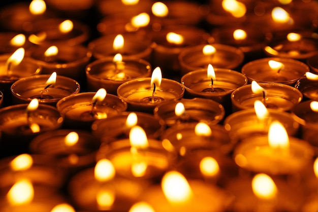 양초. 어둠 속에서 많은 불타는 초. 검은 바탕에 노란 촛불입니다.