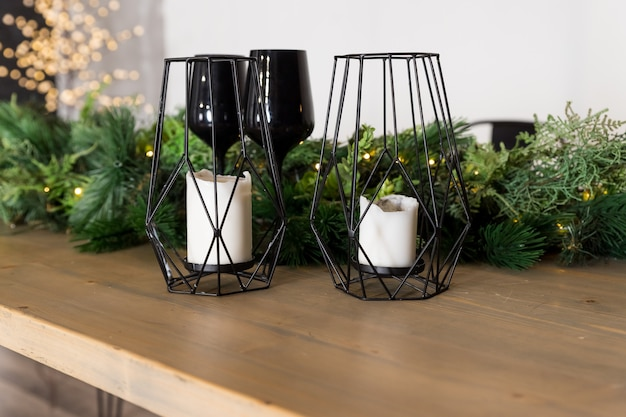 Candles in metal candle holder on wooden table with plants