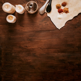 Candles near bottle and ingredients on parchment