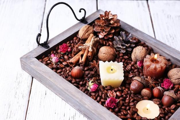 커피 곡물과 향신료가 있는 빈티지 트레이에 있는 양초, 색상 나무 배경에 범프