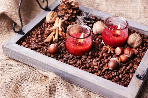 커피 곡물과 향신료가 있는 빈티지 쟁반에 있는 양초, 자루천 배경의 융기