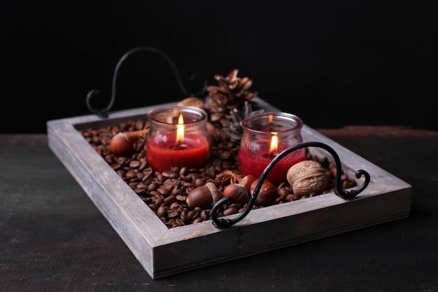 커피 곡물과 향신료가 있는 빈티지 쟁반에 있는 양초, 나무 탁자 위의 돌기, 어두운 배경