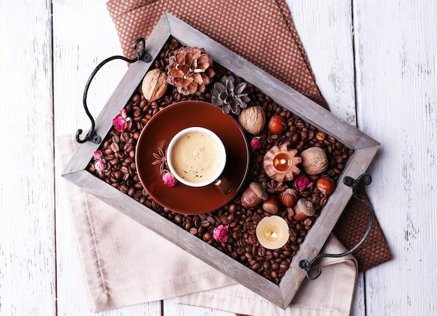 Свечи на старинном подносе с кофейными зернами и специями, чашка чая на цветном деревянном фоне