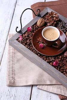 커피 곡물과 향신료를 넣은 빈티지 쟁반에 있는 양초, 색 나무 배경에 차 한 잔