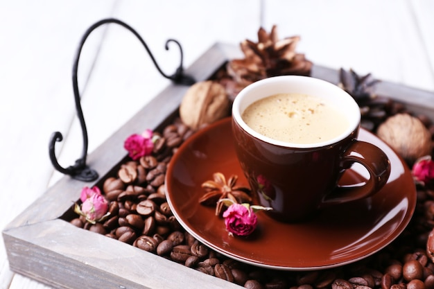 커피 곡물과 향신료를 넣은 빈티지 트레이에 있는 양초, 색 나무 표면에 차 한 잔