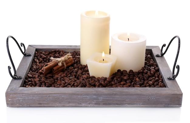 흰색으로 분리된 커피 곡물과 향신료가 있는 빈티지 트레이에 있는 양초