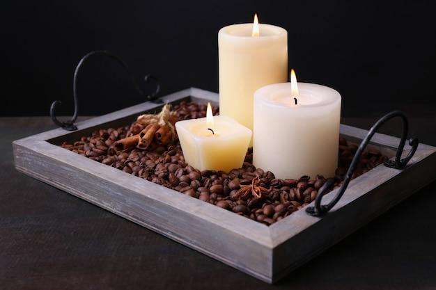 어두운 배경에 나무 테이블에 커피 곡물과 향신료와 빈티지 트레이에 촛불