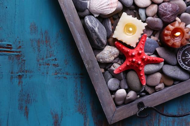 木製の背景に海の小石、ヒトデ、貝殻とビンテージトレイのキャンドル