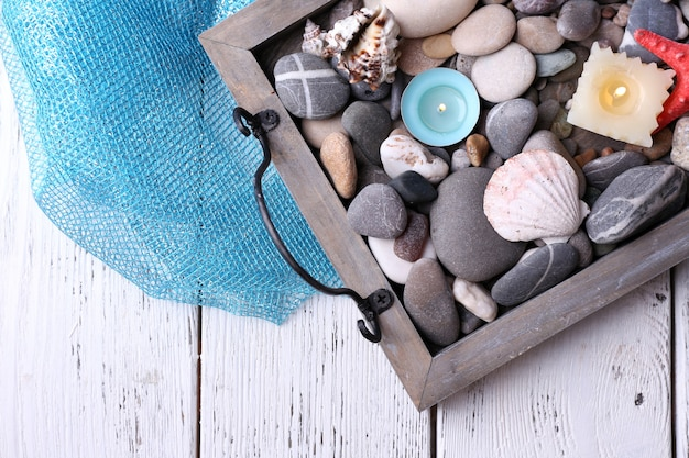木製の背景に海の小石、ヒトデ、貝殻とヴィンテージトレイのキャンドル