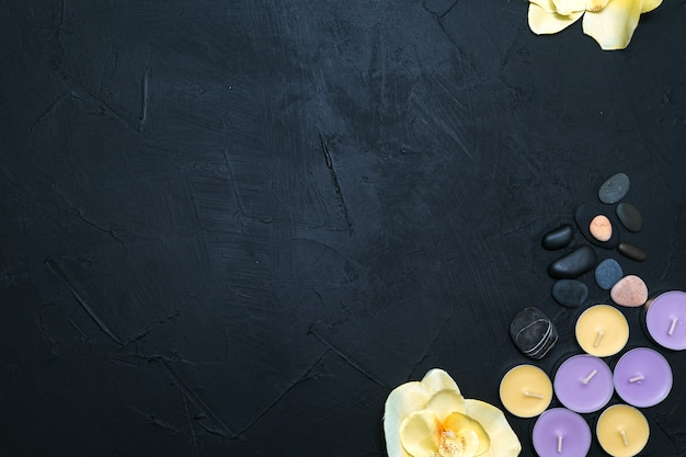 촛불, 난초 꽃과 검은 돌 배경에 자갈. 상위 뷰, 복사 공간. 스파 개념, 평면 누워.