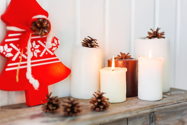 Candles, pine cones and red christmas tree