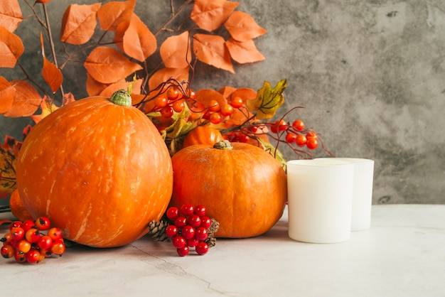 Candles and pumpkins with leaves