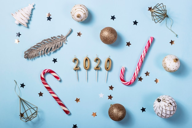 Candles in the shape of figures 2020 among christmas decorations on a blue background