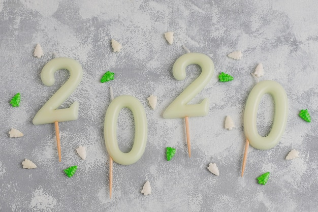 Candles in the shape of numbers 2020 as a symbol of the new year next to christmas shaped sparkle candies on a gray table. top view, flat lay