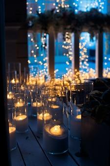 Le candele brillano sul pavimento di legno nell'oscurità