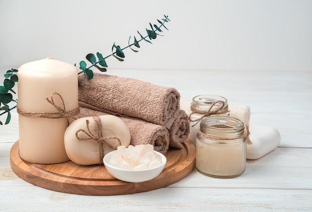 キャンドル、石鹸、白い木製の背景にユーカリの枝と茶色のタオルのセット。スパケア。