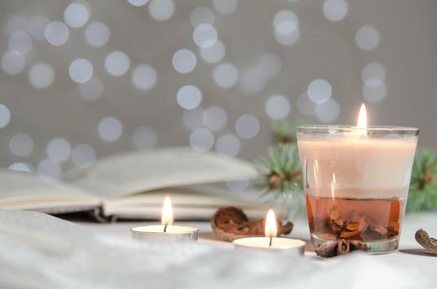 Свечи, специи и еловые ветки на фоне открытой книги
