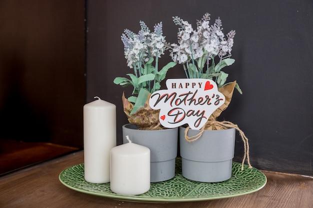 キャンドル、家の植物のある静物、背景をぼかした写真に幸せな母の日カードとピンクのバラの花束。母の日の背景。特別な日に花