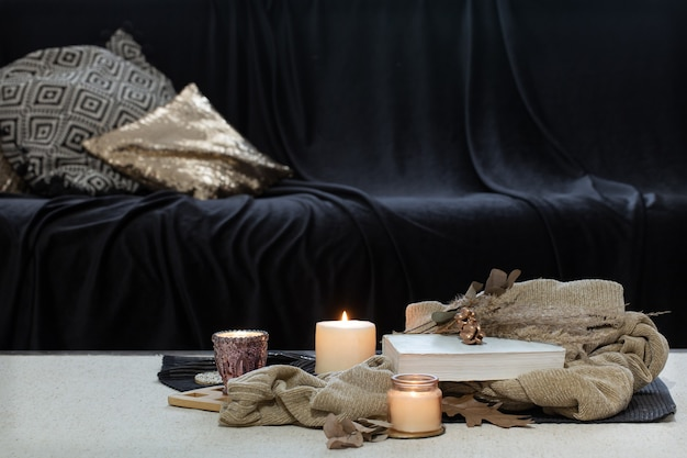 Candles, sweater and book on the table against the background of a dark sofa.