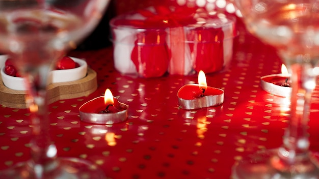 Candles for valentines day, table with festive red background.