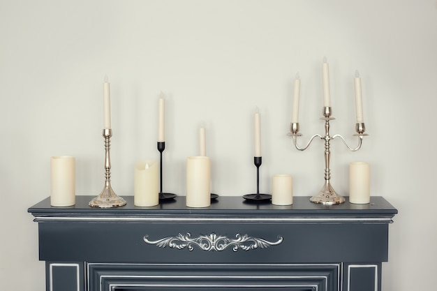 Candles of various types and sizes on the imitation fireplace countertop near the wall