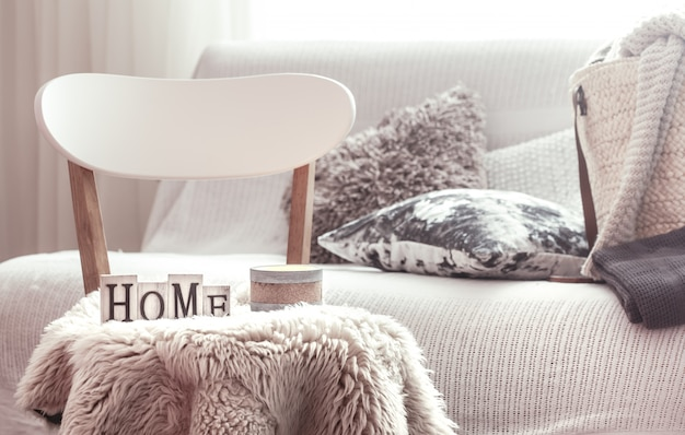 Candles, a vase with flowers with wooden letters of the home on wooden white chair. sofa and wicker basket with cushions in the background.