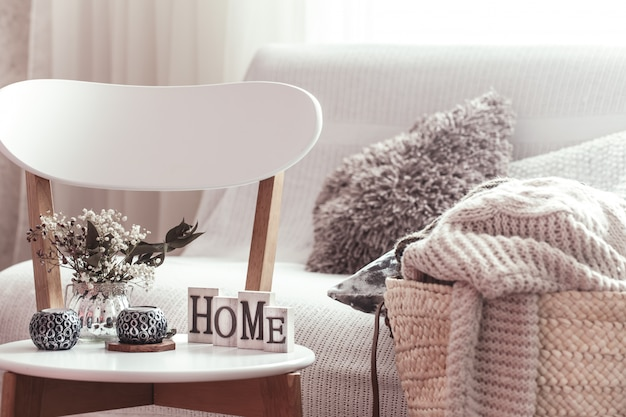 Candles, a vase with flowers with wooden letters of the home on wooden white chair. sofa and wicker basket with pillows.