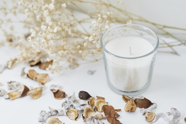 Candles with floral decor on a white table. cozy and hygge