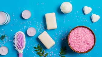 Candles with soap; bath bomb; hairbrush and pink salt on blue backdrop
