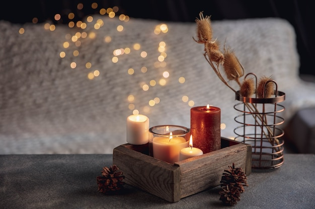 Candles in the wooden box isolated on grey white background. garland lights. the concept of home atmosphere and comfort, holidays, romantic date, winter, home comfort, indoors, christmas or new year.