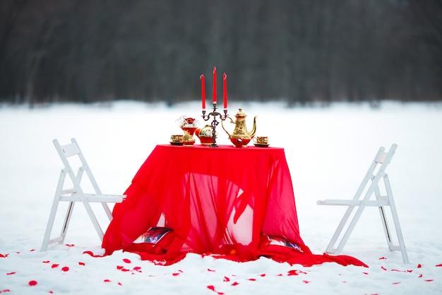 겨울 숲에서 빨간 식탁보와 테이블에 초를 가진 촛대