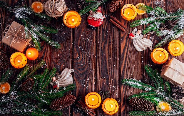 Candlesticks made of mandarins with fir branches, toys and presents on wooden table. christmas and new year