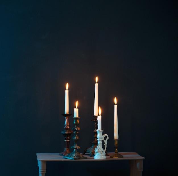 진한 파란색 배경에 촛불을 태우는 촛대