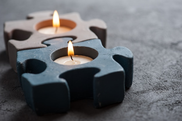 Candlesticks with burning candles on stone background