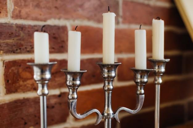 Подсвечники со свечами на фоне стены