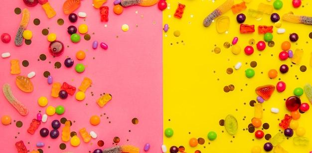 キャンディー盛り合わせレイアウト。黄ピンクの背景にキャンディーとレイアウト。歯ごたえのあるマーマレードと小さなキャラメル。明るい背景。あらゆる好みのスイーツ。お菓子についての記事。コピーspase