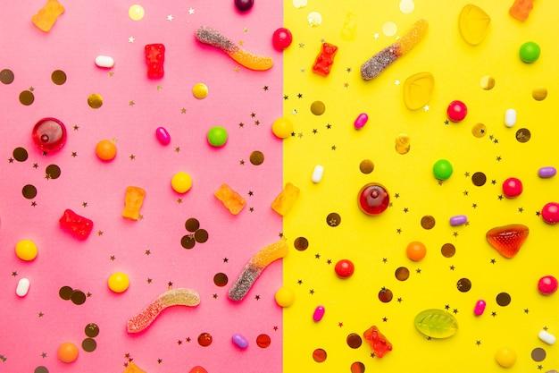 キャンディー盛り合わせレイアウト。黄ピンクの背景にキャンディーとレイアウト。歯ごたえのあるマーマレードと小さなキャラメル。明るい背景。あらゆる好みのスイーツ。お菓子についての記事。