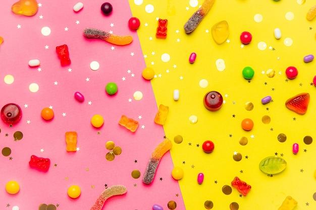 절반 분홍색과 절반 노란색 배경에 사탕 모듬 레이아웃
