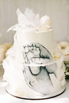 Candy bar. beautiful white cake with a picture of the child's foot, the concept of children's birthday parties