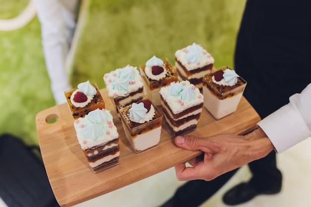キャンディーバー。カップケーキとケーキポップが付いたおいしい甘いビュッフェ。緑、青、オレンジを基調にしたカップケーキやその他のデザートの甘い休日のビュッフェ。