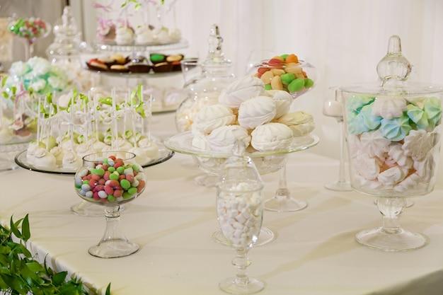 結婚披露宴用キャンディーバー結婚式用のお菓子が付いたカラフルなテーブル