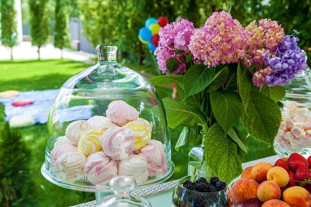 パーティー用のフルーツ、ベリー、マシュマロのキャンディーバー。甘くてフルーティーなスナックが並ぶお祭りテーブル